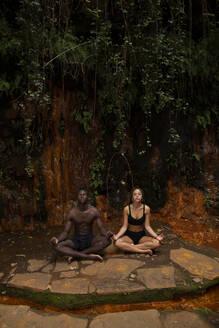 Couple meditating at a waterfall - LJF00722