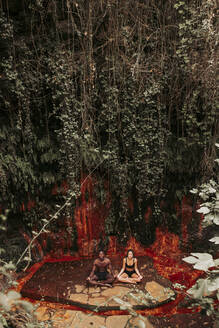 Couple meditating at a waterfall - LJF00725