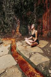 Young woman meditating at a waterfall - LJF00728