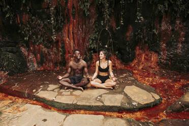 Couple meditating at a waterfall - LJF00731