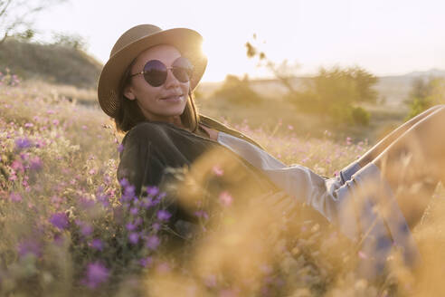 Young woman wearing sunglasses and sunhat, sitting on meadow at sunset - KNTF03080