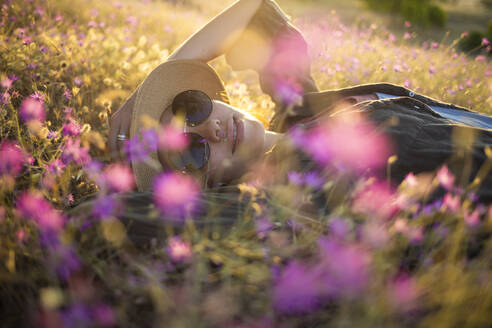 Young woman with sunhat lying on meadow at sunset - KNTF03083