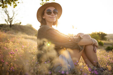 Young woman wearing sunhat and sitting on meadow at sunset - KNTF03086