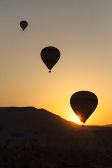 Silhouette hot air balloons flying over landscape during sunset at Goreme, Cappadocia, Turkey - KNTF03090