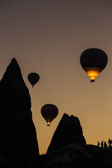 Silhouette hot air balloons flying over mountains at Goreme during sunset, Cappadocia, Turkey - KNTF03093