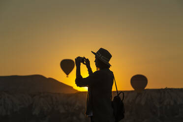 Silhouette young woman photographing with smart phone while standing on land in Cappadocia, Turkey - KNTF03096
