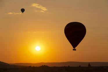 Silhouette hot air balloons flying over landscape against sky at sunset in Cappadocia, Turkey - KNTF03099