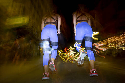 Long exposure photo of two women running in the city at night - OCMF00586