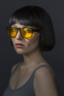 Portrait of young woman with cheek piercing and yellow glasses - VGF00296
