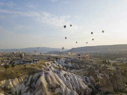 Aerial view of colorful hot air balloons flying against sky at Goreme National Park, Cappadocia, Turkey - KNTF03146