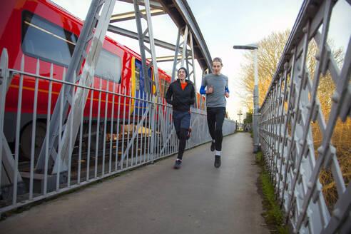 Two teenagers running over railway bridge - AJOF00002