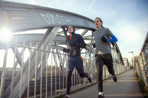 Two teenagers running over railway bridge - AJOF00005