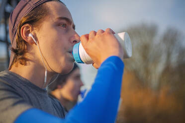 Two teenagers drinking water after a run - AJOF00011