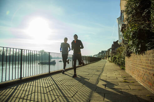 Two teenagers jogging along River Thames, London, UK - AJOF00014