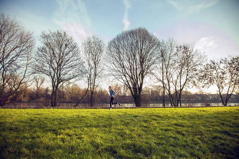 Young man jogging in a park - AJOF00017