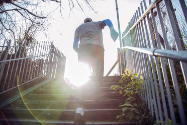 Young man running up steps for exercise - AJOF00020