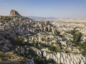 Aerial view of Uchisar castle and buildings against blue sky in Cappadocia, Turkey - KNTF03150