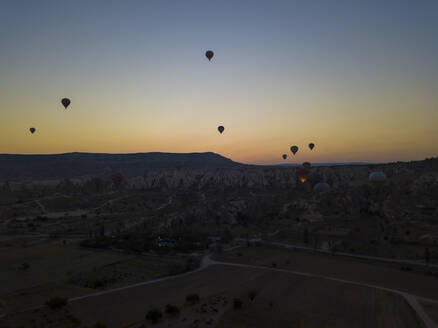 Silhouette hot air balloons flying over landscape against clear sky during sunset, Cappadocia, Turkey - KNTF03219