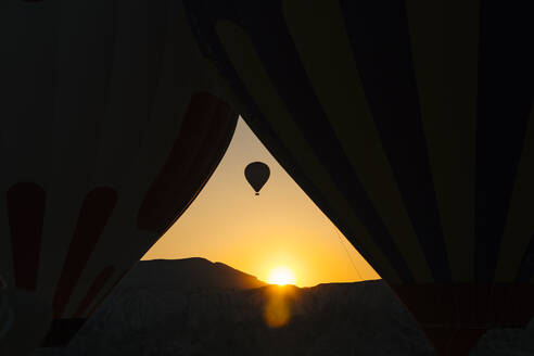 Silhouette hot air balloon flying against clear sky seen through tent during sunset, Cappadocia, Turkey - KNTF03247
