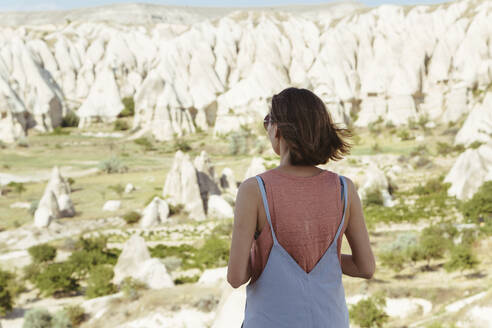 Rear view of young woman looking at rocky landscape while standing in Goreme village, Cappadocia, Turkey - KNTF03253