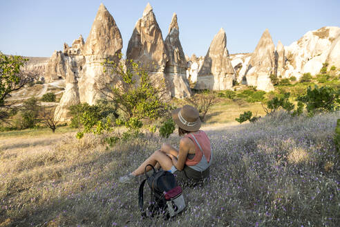 Side view of young woman sitting on land at Goreme village, Cappadocia, Turkey - KNTF03259