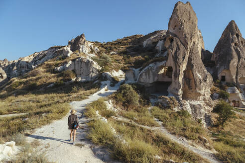 Rear view of young woman walking on road against clear blue sky in Goreme, Cappadocia, Turkey - KNTF03268