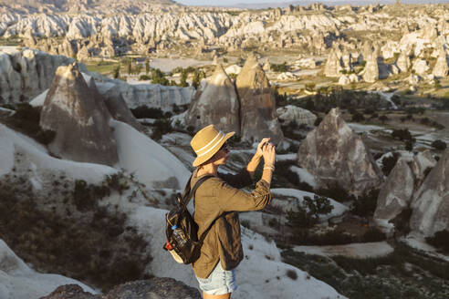 Side view of young woman photographing rock formations with smart phone in Goreme, Cappadocia, Turkey - KNTF03271