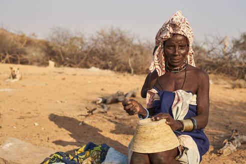 Mucubal tribe woman sewing a traditional pot, Tchitundo Hulo, Angola. - VEGF00564