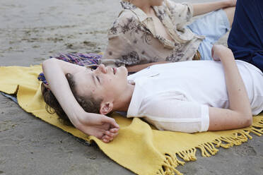 Friends relaxing on beach, daydreaming, lying on blanket - AMEF00068