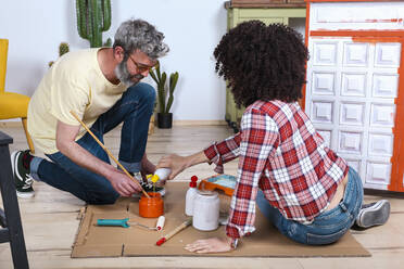 Couple painting furniture with brush at home - RTBF01352
