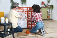 Couple painting furniture with brush at home - RTBF01355