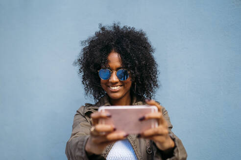 Almeria, Spain. Woman using smartphone on blue background. - MPPF00019
