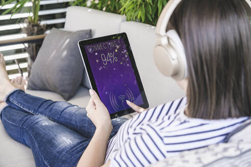 Young woman with tablet awith smart home control functions and headphones - UUF18840