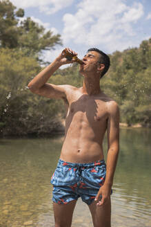 Boy in swimsuit in a lake drinking beer. Angues, Huesca, Spain. - ACPF00606