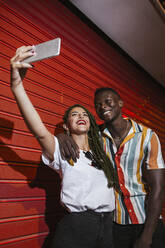 Happy young couple taking a selfie at red roller shutter at night - LJF00779