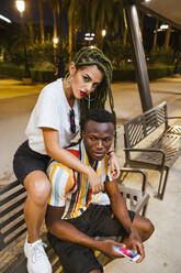 Cool young couple on a bench at night in the city - LJF00782