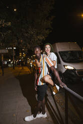 Happy young couple on the street at night in the city - LJF00788