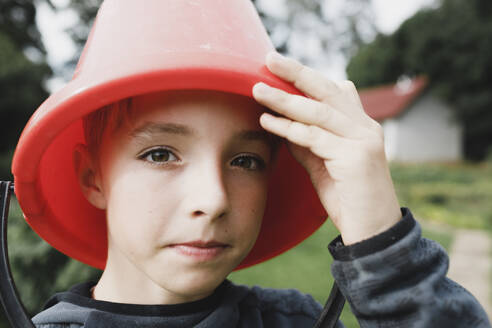 Portrait of a boy with a red bucket on his head - KMKF01038