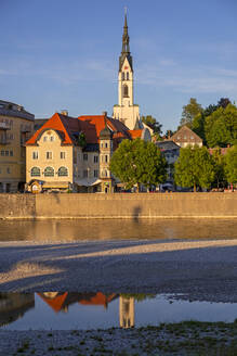 Parish Church of the Assumption and buildings by River Isar against sky in town, Bavaria, Germany - LBF02673