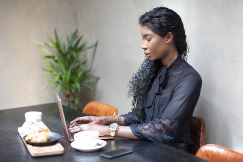 Chic businesswoman using laptop at table in a cafe - ALBF00984