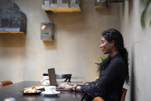Chic businesswoman using laptop at table in a cafe - ALBF00987