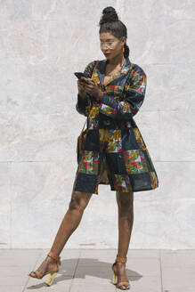 Portrait of chic woman wearing patterned dress using cell phone - ALBF01005
