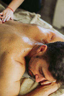 Man receiving a back massage in a spa - LJF00867