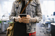 Student with tattoos using smartphone close up - HEROF37947