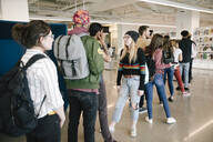 Students standing in university library talking - HEROF38024