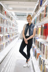 Portrait of student leaning on bookshelf in library and smiling - HEROF38033