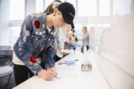 Student wearing denim jacket and cap making notes in classroom - HEROF38162