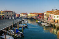 View of Ponte San Martino stone bridge over canal with colorful buildings and moored boats on wooden wharf pilings, Venice, UNESCO World Heritage Site, Veneto, Italy, Europe - RHPLF05862