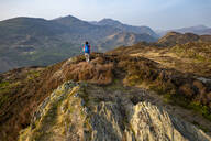 A woman trekking in Snowdonia walks across the top of Mynydd Sygun near Bedgellert with views of Mount Snowdon in the distance, Gwynedd, Wales, United Kingdom, Europe - RHPLF06297