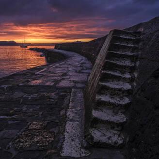 Twilight with Irene anchored off The Cobb in Lyme Regis, Dorset, England, United Kingdom, Europe - RHPLF06372